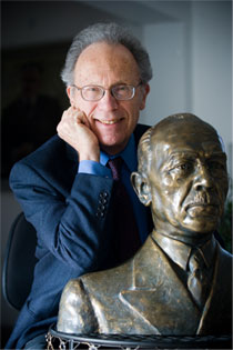 Portrait of John Palka next to a bronze bust of Milan Miloslav Hodza.